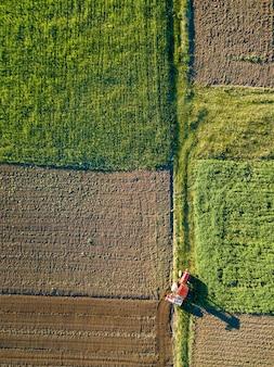 Forme geometriche astratte di campi agricoli con diverse colture e terreno senza semina, separati da strada e trattore su di esso, nei colori verde e nero. una vista a volo d'uccello dal drone.