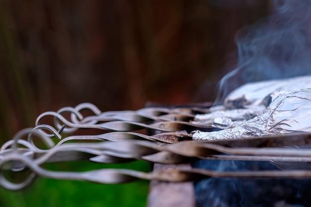 Vista altamente sfocata astratta di spiedini di metallo sdraiati su una griglia sopra i carboni. fumo profumato. appetitosa delicatezza di carne naturale all'aria aperta in una giornata primaverile.