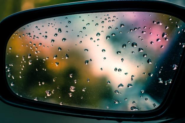 Immagine astratta di gocce di pioggia sullo specchietto retrovisore laterale dell'auto