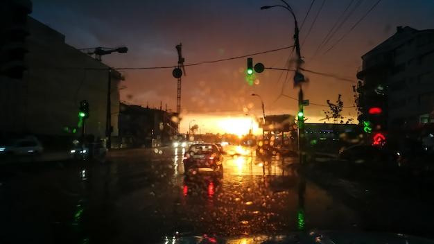 Immagine astratta attraverso il parabrezza bagnato dell'auto sul trasporto in movimento e autuomobiles sotto la pioggia ai raggi del tramonto