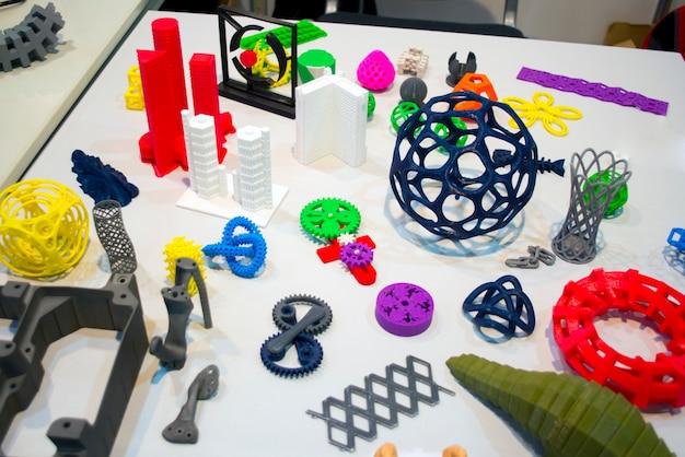 Modelli astratti stampati dal primo piano della stampante 3d. oggetti colorati luminosi stampati su una stampante 3d su un tavolo bianco. tecnologia additiva moderna e progressiva. concetto di rivoluzione industriale 4.0