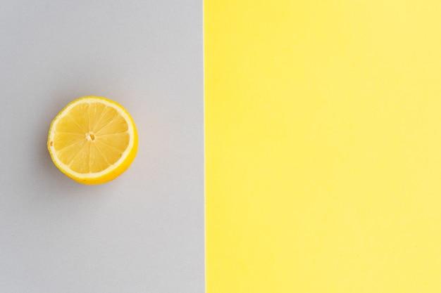 Sfondo astratto moderno di carta fatta a mano con metà limone nei colori grigio e giallo illuminanti