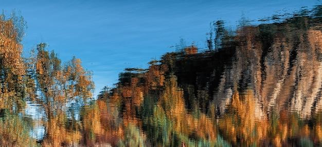 Sfondo naturale astratto. riflessione di un bosco autunnale nell'acqua di un lago di montagna