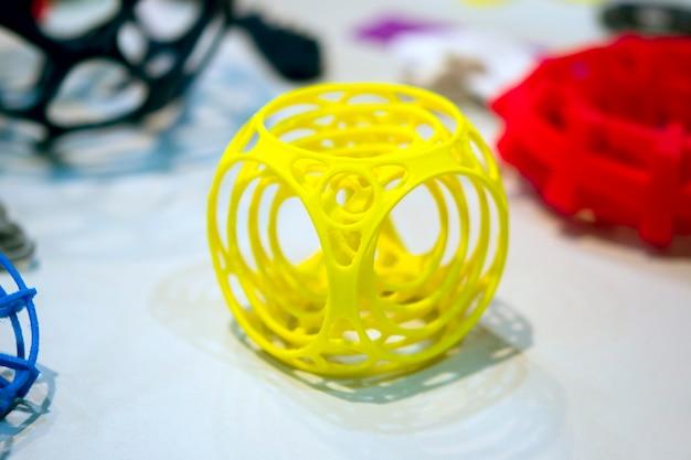 Oggetto astratto di colore giallo stampato su una stampante 3d su un tavolo bianco. modellazione a deposizione fusa, fdm. tecnologia additiva moderna e progressiva. concetto di rivoluzione industriale 4.0