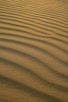 Il modello astratto della sabbia del deserto si increspa alla luce solare di sera alla duna di sabbia di huacachina dentro