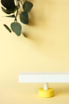 Piedistallo astratto su sfondo giallo pastello con spazio di copia e foglie di eucalipto sfocati, vista frontale.