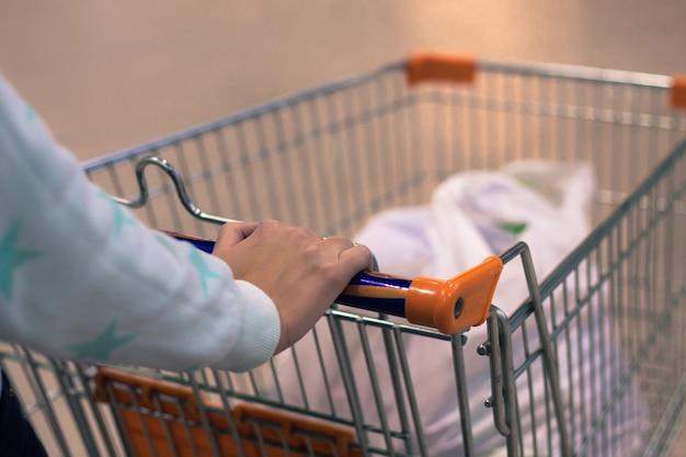 Foto astratta di una donna che fa rotolare un carrello o un carrello in un supermercato con sfondo sfocato