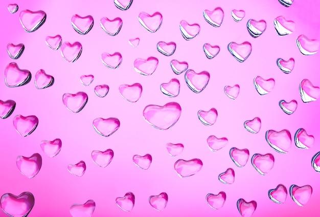 Astratto sfondo rosa con cuori di gocce d'acqua. astrazione d'amore. simbolo del giorno di san valentino. texture brillante, pattern.