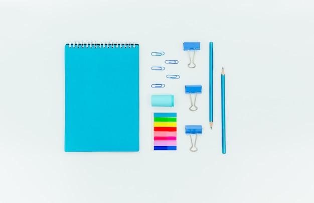 Tavola rossa astratta con stazionario. taccuino in bianco e forbici, pensils, penne. flatlay vista orizzontale superiore copyspace.