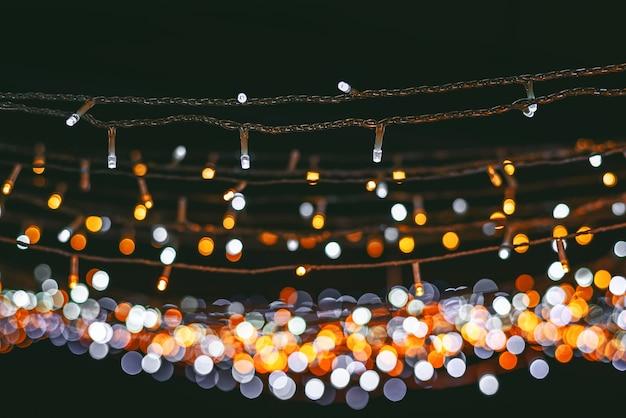 Fondo rosso e giallo astratto del bokeh della luce della lampadina, concetto del buon anno e di natale