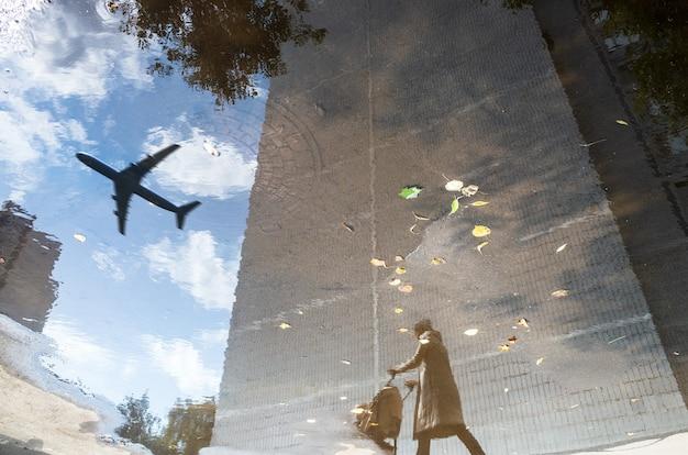 Riflessione astratta di una strada cittadina in una pozzanghera di pioggia aereo volante