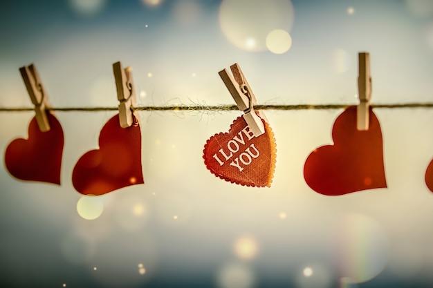 Disegno romantico astratto con cuori rossi su mollette