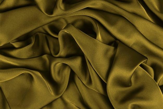 Panno di seta satinato astratto, tessuto in tessuto drappeggiato con pieghe ondulate piegate. con onde morbide, ondeggianti al vento. trama di carta stropicciata