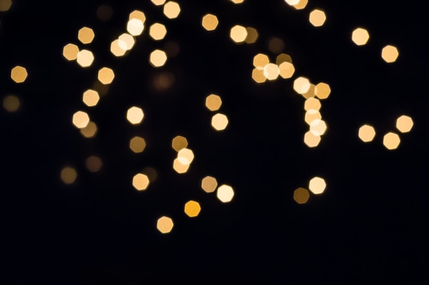 Scattering astratto di luci dorate su sfondo nero. concetto di vacanza.