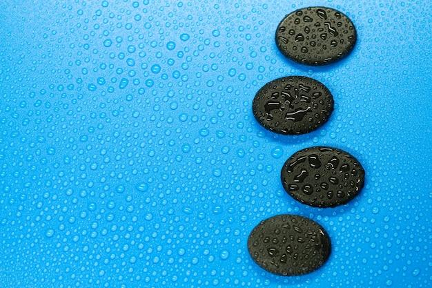 Disegno astratto spa di gocce d'acqua e pietre del bilanciamento del nero su sfondo blu