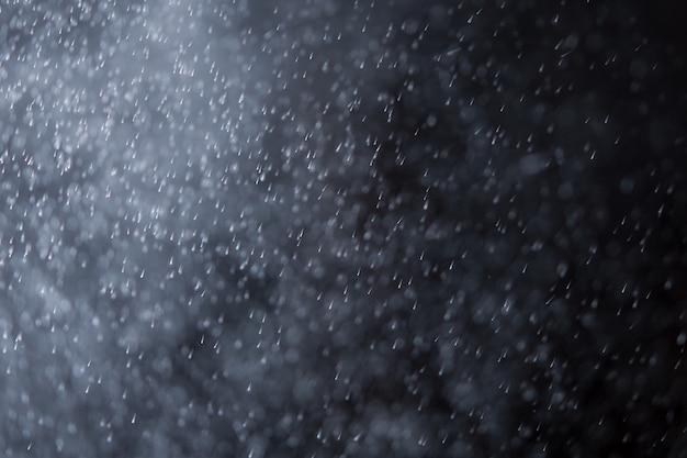 L'estratto spruzza dell'acqua o della neve su una priorità bassa scura