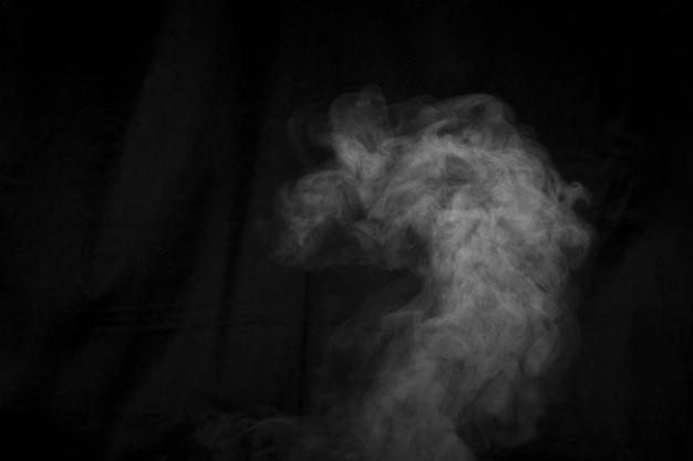Vapore astratto con punti di spruzzo si muove su uno sfondo nero. il fumo figurato può essere utilizzato per il design.