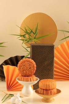 Abstract still life mid autumn festival snack torta di luna su sfondo color crema con giovane albero di bambù, messa a fuoco selezionata, copia spazio per text