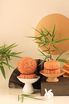 Abstract still life mid autumn festival snack torta di luna su sfondo color crema con giovane albero di bambù, messa a fuoco selezionata