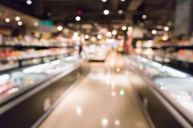 Il frigorifero astratto della drogheria del supermercato ha offuscato il fondo defocused con la luce del bokeh