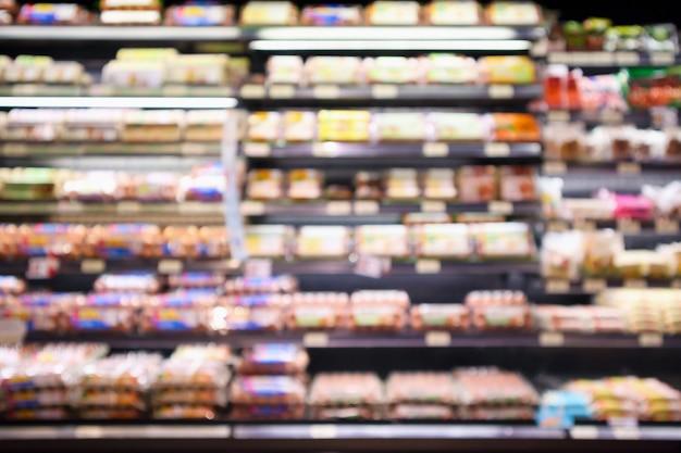 La drogheria astratta del supermercato con gli scaffali dell'uovo ha offuscato il fondo defocused con la luce del bokeh