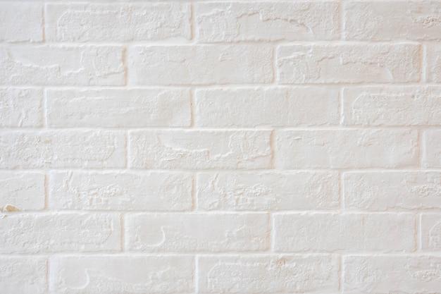 Fondo bianco strutturato esposto all'aria astratto del muro di mattoni