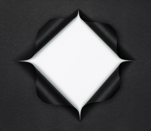 Forma bianca astratta su carta nera strappata