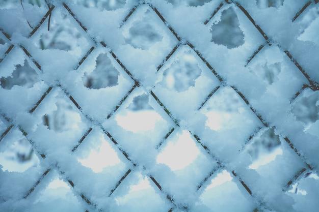 Priorità bassa astratta di inverno. neve sulla griglia metallica