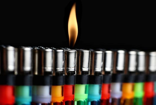 Astratto con accendini colorati e una sola fiamma