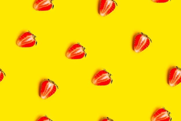 Estratto con fragole fresche rosse su colore giallo.