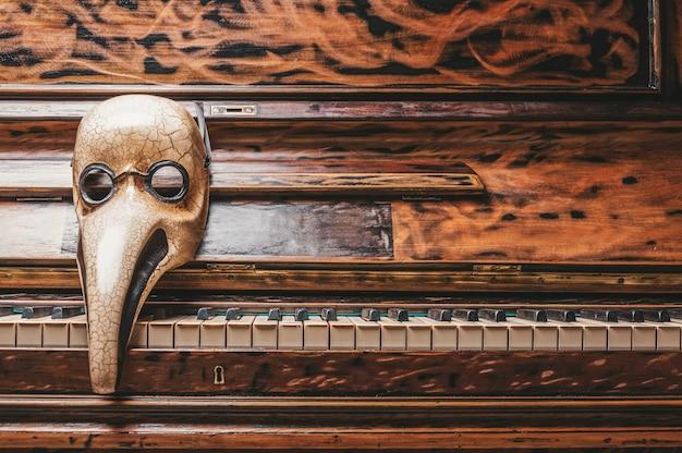 Astrazione di una maschera veneziana di un medico sdraiato sui tasti del pianoforte