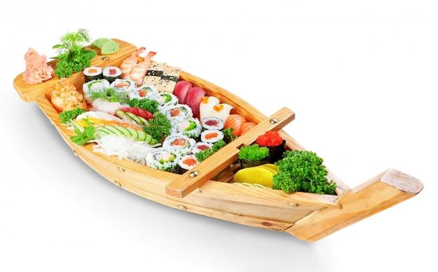 Abbondanza di piatti orientali di sushi con ingredienti freschi sul piatto della nave. su un muro bianco