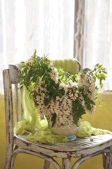 Fiori di acacia in vaso bianco. natura morta con fiori di acacia su vintage shair.