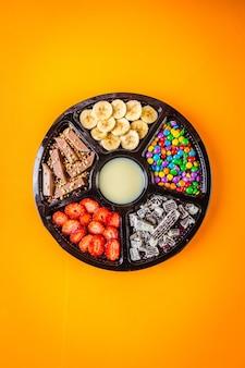 Acai congelato con banana, muesli, cioccolato e caramelle da condividere.