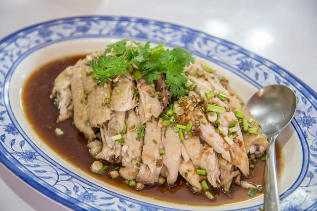 Accent pollo al vapore con coriandolo su un piatto di fondo soft focus.
