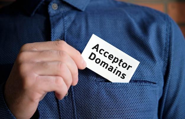 Testo del dominio dell'accettore su un segno bianco nella mano di un uomo in camicia