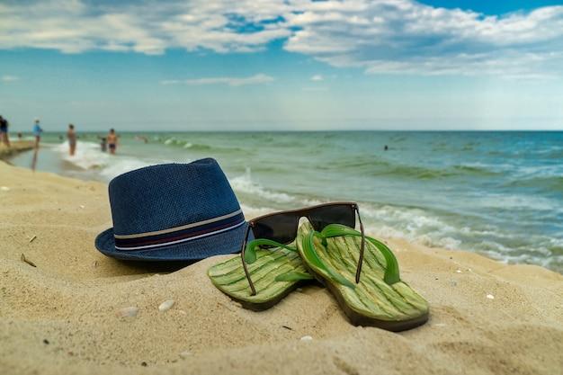 Accessori per la spiaggia sdraiata sulla sabbia, pantofole da uomo e occhiali da sole sulla sabbia della spiaggia
