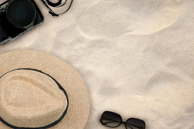 Accessori costume per la gita su sabbia sullo sfondo spiaggia. vista dall'alto