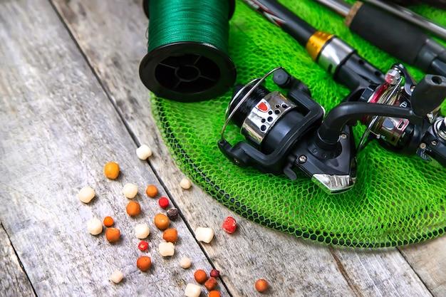Accessori per la pesca su uno sfondo di legno. messa a fuoco selettiva. pesca.