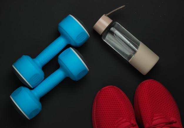 Accessori per fitness e sport su sfondo nero. manubri, scarpe sportive, una bottiglia d'acqua. vista dall'alto, piatto
