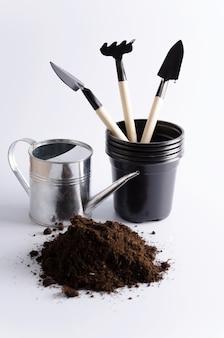 Accessori per piantare e coltivare ortaggi a casa. orto a casa, terra, irrigazione, vasi di plastica, pala e rastrello, immagine verticale