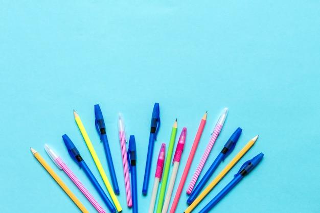 Accessori per la scuola, quaderni, penne, matite per il posto di lavoro di uno scolaro su sfondo blu