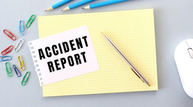 La relazione di incidente è scritta su un pezzo di carta che si trova su un taccuino accanto alle forniture per ufficio. concetto di affari.