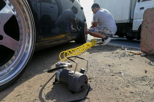 Incidente sulla pressione della gomma a terra un uomo gonfia una ruota di un'autovettura con un compressore