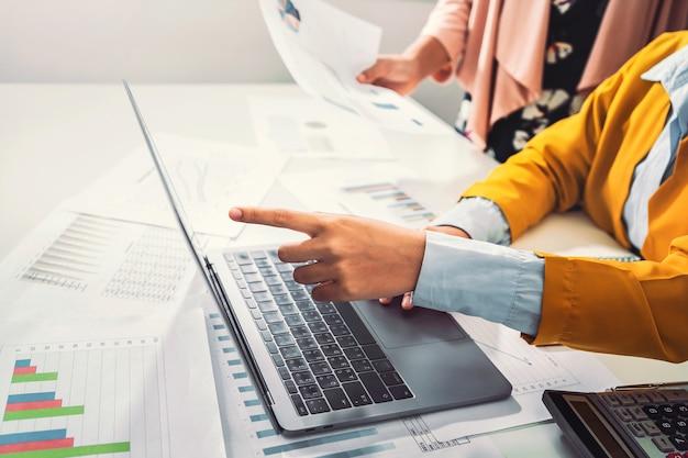 Ragioniere che indica sul computer portatile per la riunione del gruppo nella stanza dell'ufficio. concetto di finanza e contabilità