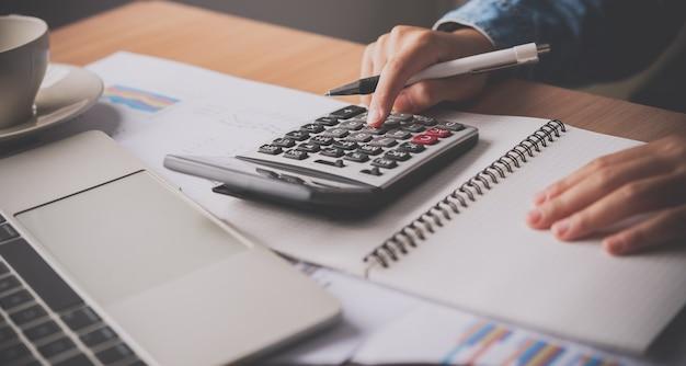La mano del ragioniere sta usando la calcolatrice. per l'analisi dei costi profitti e perdite e concetto di calcolo delle imposte preparazione di rendiconti finanziari