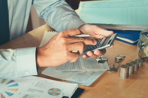 Ragioniere che utilizza la calcolatrice calcola il budget per il salvataggio. concetto di finanza e contabilità