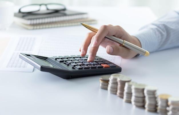 Ragioniere che per mezzo del calcolatore per il controllo dei numeri dal bilancio e dagli statemen finanziari