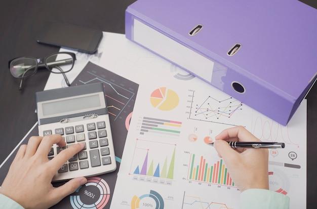 Ragioniere con il grafico del documento finanziario sulla tavola dell'ufficio.