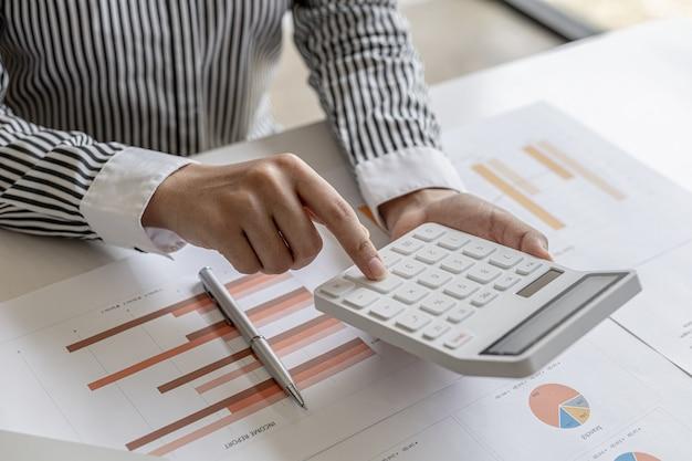 Una studiosa di ragioneria preme una calcolatrice, calcola i numeri riportati sui documenti di conto economico e finanziario della società, è revisore contabile di società. concetto di revisione.